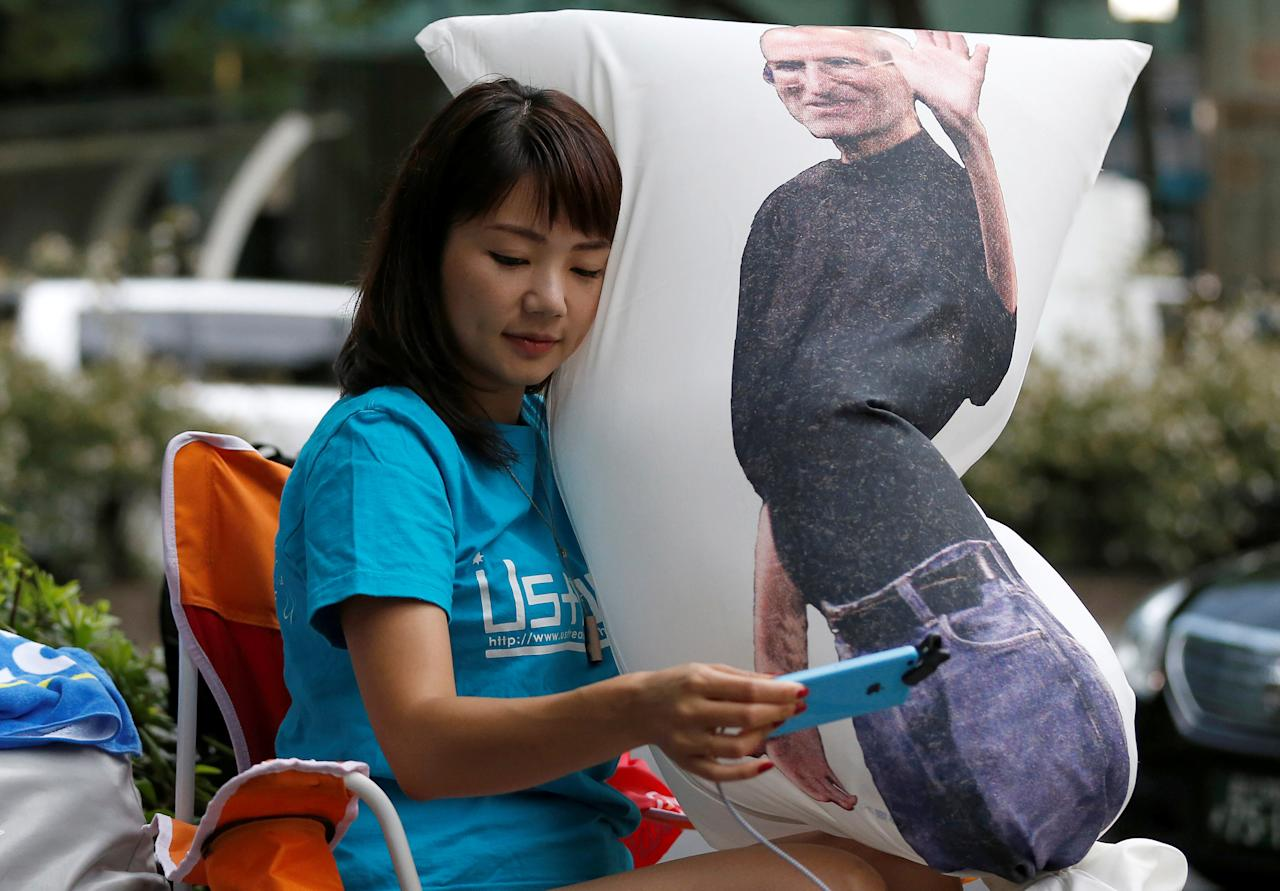 Ayano Tominaga holds a cushion printed a portrait of Apple co-founder Steve Jobs on it, as she sits in queue for the release of Apple's new iPhone 7 and 7 Plus in front of the Apple Store in Tokyo's Omotesando shopping district, Japan, September 16, 2016.    REUTERS/Issei Kato