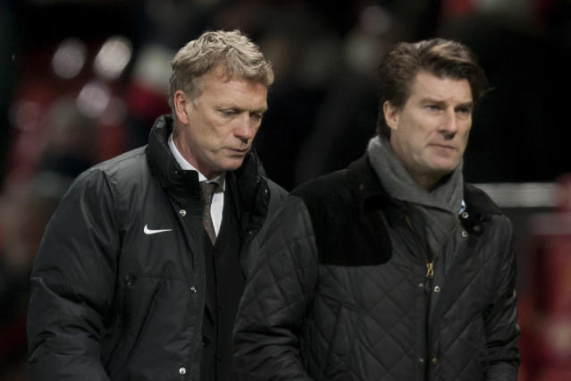 Manchester United's manager David Moyes, left, walks from the pitch behind opposition manager Michael Laudrup after his team's 2-1 loss to Swansea City in their English FA Cup third round soccer match at Old Trafford Stadium, Manchester, England, Sunday Jan. 5, 2014. (AP Photo/Jon Super)