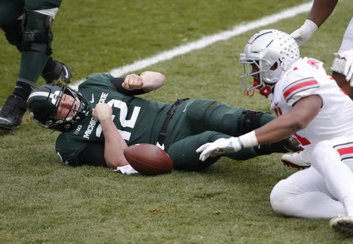 Michigan State quarterback Rocky Lombardi, left, reacts after being sacked by Ohio State's Tyreke Smith, right, during the first half of an NCAA college football game, Saturday, Dec. 5, 2020, in East Lansing, Mich. Lombardi was injured on the play and left the game. (AP Photo/Al Goldis)