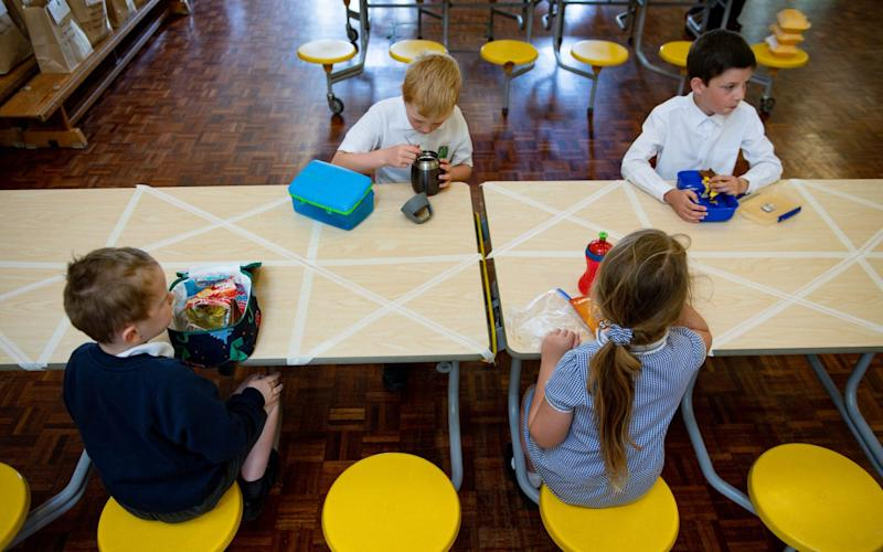 Children of essential workers eat lunch in segregated positions at Kempsey Primary School in Worcester. - PA
