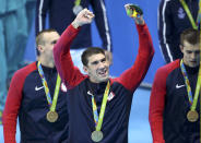 <p>Michael Phelps poses with his gold medal as he celebrates with his team at the victory ceremony for the men's 4 x 100m freestyle relay event on August 7, 2016 in Rio. (REUTERS/Marcos Brindicci)</p>