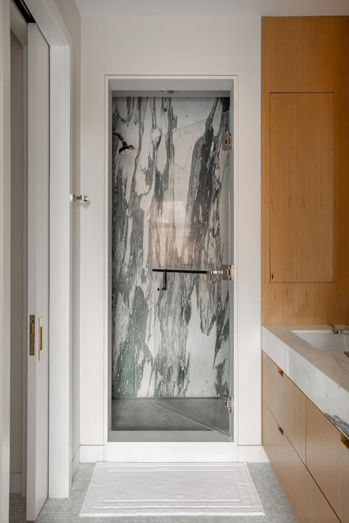 "<div class=""caption""> ""I purchased two slabs of marble from Italy well before we started construction, and these served as the first design dominos to fall for the entire apartment,"" says Clayton. ""The shower became a real <em>moment</em> for the apartment, and every morning when I wake up I can see it in the distance, and it feels like a piece of art."" </div>"