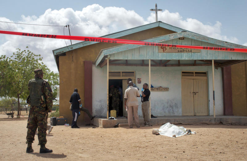 Members of the Kenyan security forces inspect the scene, as a body lies covered by a sheet, outside the African Inland Church in Garissa, Kenya Sunday, July 1, 2012. Gunmen killed two policemen guarding a church, snatched their rifles and then opened fire on the congregation with bullets and grenades on Sunday, killing at least 10 people and wounding at least 40, security officials said, with militants from Somalia being immediately suspected. (AP Photo/Chris Mann)