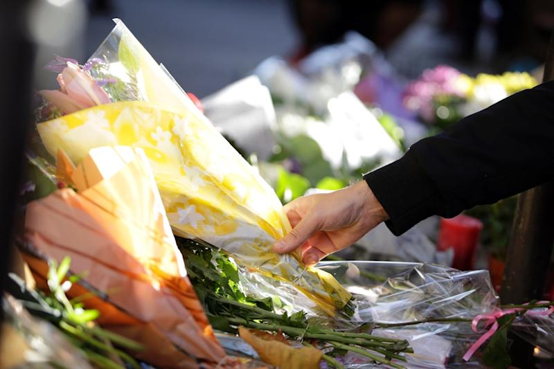 """A man places flowers in front of the """"Bonne biere"""" cafe in Paris on November 15, following a series of coordinated attacks in and around the French capital"""