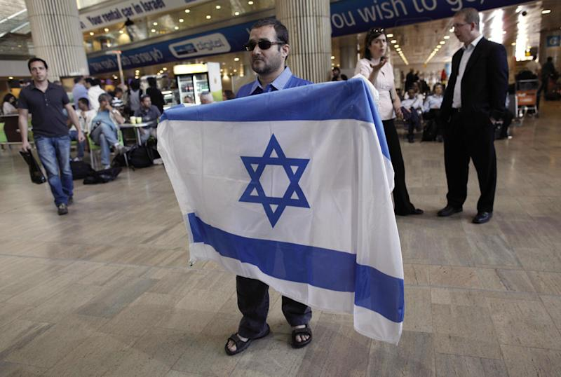 An activist holds an Israeli flag in protest against a pro-Palestinian campaign expected to arrive at Ben Gurion Airport near Tel Aviv, Israel, Sunday, April 15, 2012. Israel deployed hundreds of police Sunday at its main airport to detain activists flying in to protest the country's occupation of Palestinian areas, defying vigorous Israeli government efforts to block their arrival. (AP Photo/Tsafrir Abayov)