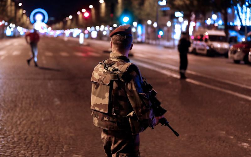 A French soldier stands guard during ongoing police operations - Credit: EPA