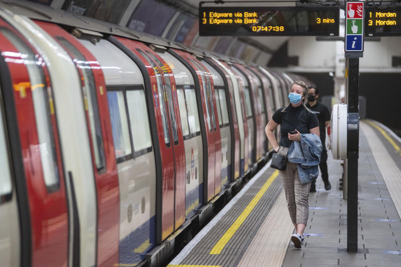 A commuter wearing a protective face mask walks along the platform at Clapham Common underground station, London, as train services increase this week as part of the easing of coronavirus lockdown restrictions, Thursday May 21, 2020. (Dominic Lipinski/PA via AP)