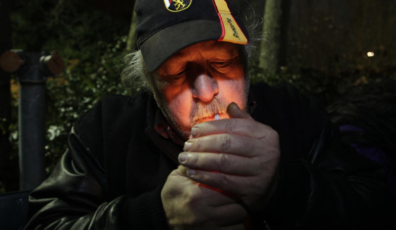 Mike Momany smokes marijuana, Thursday, Dec. 6, 2012, just after midnight at the Space Needle in Seattle. Possession of marijuana became legal in Washington state at midnight, and several hundred people gathered at the Space Needle to smoke and celebrate the occasion, even though the new law does prohibit public use of marijuana. (AP Photo/Ted S. Warren)