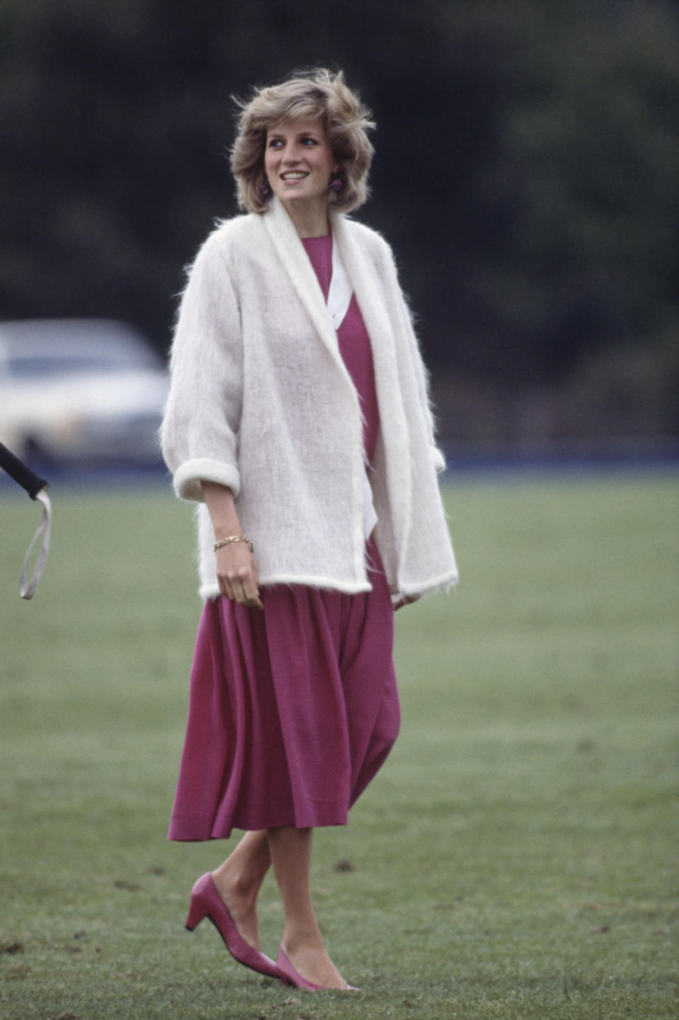 <p>Princess Diana wears a hot-pink dress and fuzzy cream sweater at the Guards Polo Club in Windsor. (Photo: Getty Images) </p>