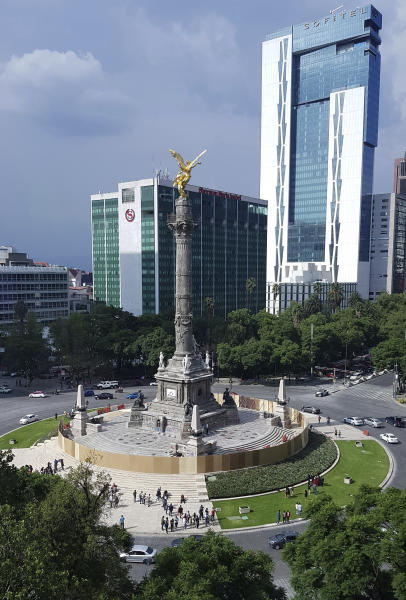 Mexican officials cordon off the iconic Angel of Independence monument after protesters defaced it with graffiti, in Mexico City, Saturday, Aug. 17, 2019. Protests erupted in the capital this week over a perception that city officials were not adequately investigating recent rape accusations. (AP Photo/Amy Guthrie)