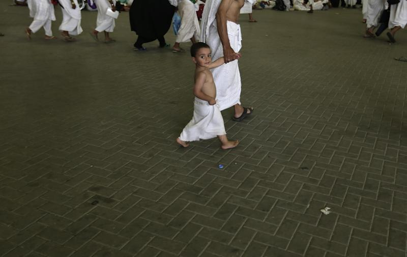 "Youssef, 3, a muslim pilgrim from Egypt walks with his grandfather to casts stones at a pillar, symbolizing the stoning of Satan, in a ritual called ""Jamarat,"" the last rite of the annual hajj, in Mina near the Saudi holy city of Mecca, Saudi Arabia, Friday, Oct. 26, 2012. (AP Photo/Hassan Ammar)"