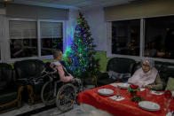 Two elders wait Christmas eve dinner at an elderly care home in Pozuelo de Alarcon, outskirts of Madrid, Thursday, Dec. 24, 2020. Many of the elderly in the residence haven't celebrate Christmas eve with their relatives to prevent the spread of coronavirus (AP Photo/Bernat Armangue)