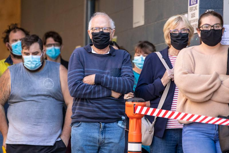 People are seen lining up to be tested for COVID at a testing clinic at Ipswich Hospital. Source: Getty