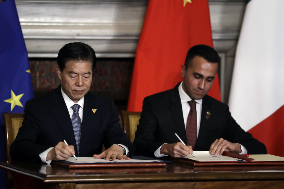 """China's Commerce Minister Zhong Shan, left, and Italian Labor Minister Luigi Di Maio sign a memorandum of understanding at Rome's Villa Madama, Saturday, March 23, 2019. Italy signed a memorandum of understanding with China on Saturday in support of Beijing's """"Belt and Road"""" initiative, which aims to weave a network of ports, bridges and power plants linking China with Africa, Europe and beyond. (AP Photo/Andrew Medichini)"""
