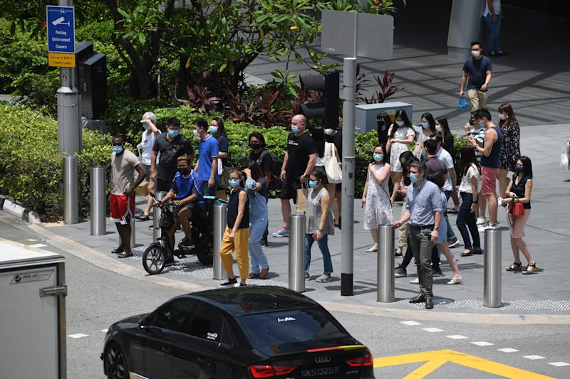 Pedestrians wait to cross the street at a junction along the Orchard Road shopping district in Singapore on September 25, 2020. (Photo by ROSLAN RAHMAN / AFP) (Photo by ROSLAN RAHMAN/AFP via Getty Images)