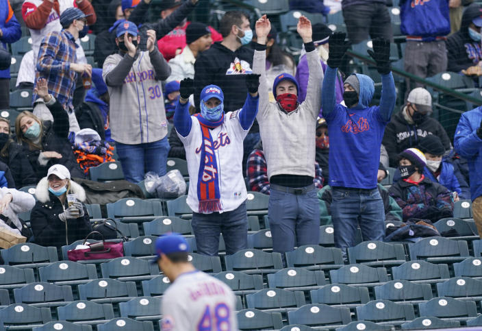Fans celebrate as New York Mets starting pitcher Jacob deGrom heads to the dugout after striking out Colorado Rockies' C.J. Cron to end the fourth inning of the first baseball game of a doubleheader Saturday, April 17, 2021, in Denver. (AP Photo/David Zalubowski)