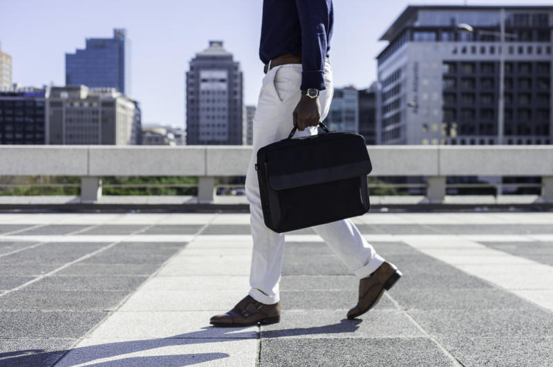 Mid adult African businessman walking through the city holding his laptop bag, the man is well dressed and the image is taken from the waist down.