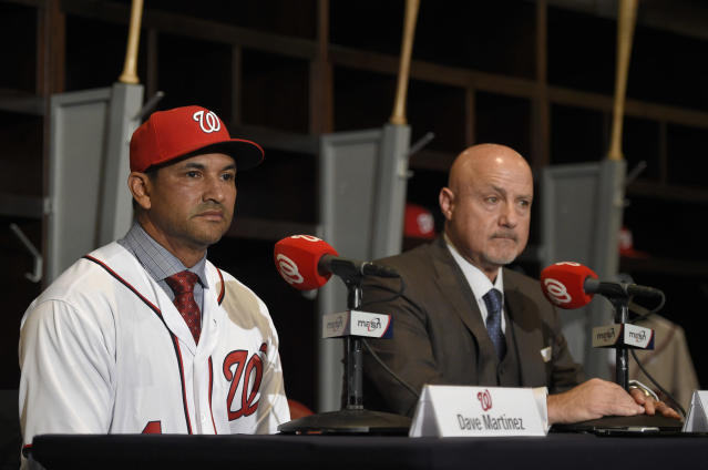 FILE - In this Nov. 2, 2017, file photo, Washington Nationals manager Dave Martinez, left, looks on next to general manager Mike Rizzo, right, as he speaks during a baseball news conference in Washington. As the start of spring training approaches, the Washington Nationals are waiting right along with the rest of the world to find out where Bryce Harper will be playing next season. (AP Photo/Nick Wass, File)