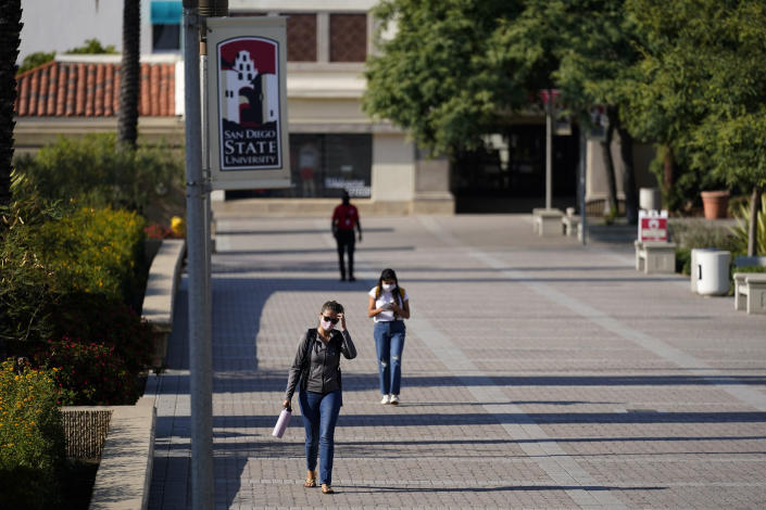 FILE - In this Sept. 2, 2020, file photo, people walk on campus at San Diego State University in San Diego. Officials in college towns all over the U.S. are fretting that off-campus students are being counted in places other than the communities where their schools are located. (AP Photo/Gregory Bull, File)