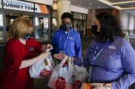 Volunteer Joan Kearl hands food to Wendy Haralson, right, and Amber Wilson outside a hotel Friday, March 26, 2021, in San Antonio. Kearl picked up the food for the quarantined Louisville women's basketball team participating in the NCAA tournament. The NCAA and local organizing groups set up expanded ambassador and item-delivery services relying on volunteer help to take care of needs for players, officials and others working inside. (AP Photo/Morry Gash)