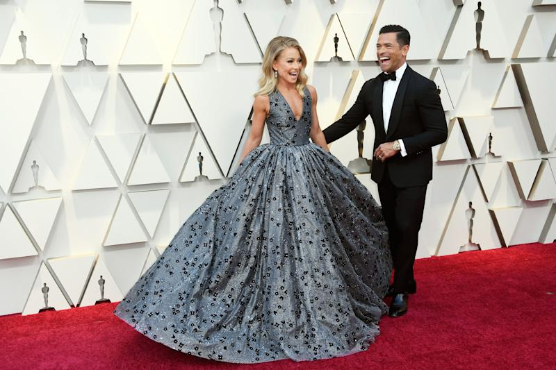 Kelly Ripa adorns in a ball dress with print desigs sharing a smile with Mark Consuelos who is dressed in black suit and pant to match