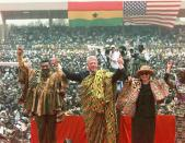 FILE - In this Monday, March 23, 1998 file photo, Ghana's President Jerry Rawlings, left, U.S. President Clinton, center, and U.S. First Lady Hillary Rodham Clinton, center-right, both wearing the Kente traditional Ghanaian dress, and Ghana's first lady Nana Rawlings, right, greet a crowd of over 200,000 people assembled in Independence Square in Accra, Ghana. Ghana's former president Jerry Rawlings, who staged two coups and later led the West African country's transition to a stable democracy, has died aged 73, according to the state's Radio Ghana and the president Thursday, Nov. 12, 2020. (AP Photo/Greg Gibson, File)