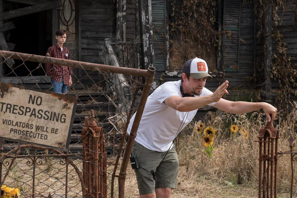 <em>Mama</em> director Andy Muschietti on set outside the house on Neibolt street where the Losers Club track down Pennywise. The the background stands Jaeden Lieberher, who plays Stuttering Bill. (Warner Bros.)