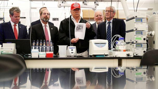 PHOTO: President Donald Trump displays a photo of the COVID-19 Coronavirus during a tour of the Center for Disease Control in Atlanta, March 6, 2020. (Tom Brenner/Reuters)