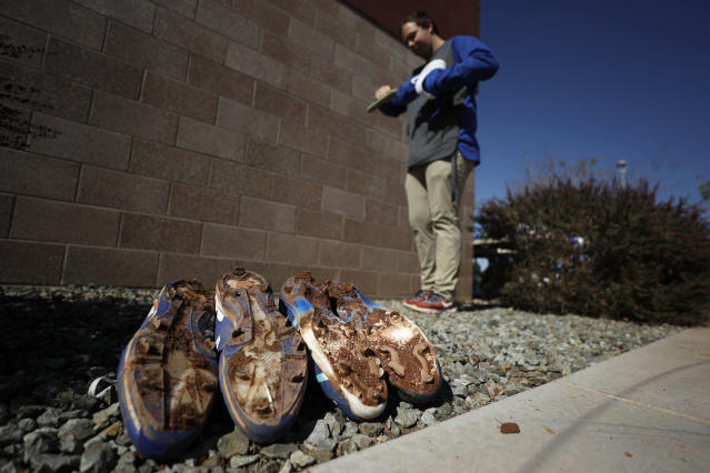 Chicago Cubs clubhouse assistant Andy Hagberg cleans cleats during a spring training baseball workout Wednesday, Feb. 12, 2020, in Mesa, Ariz. (AP Photo/Gregory Bull)