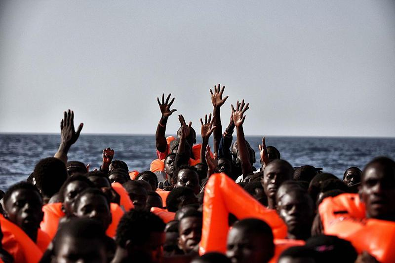 People gesture for help as they drift in the Mediterranean Sea some 20 nautical miles north off the coast of Libya on 3 October 2016: AFP/Getty