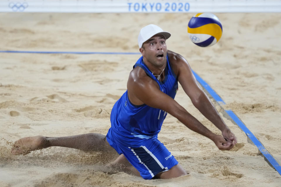Adrian Ignacio Carambula Raurich, of Italy, dives for the ball during a men's beach volleyball match against Qatar at the 2020 Summer Olympics, Wednesday, July 28, 2021, in Tokyo, Japan. (AP Photo/Petros Giannakouris)
