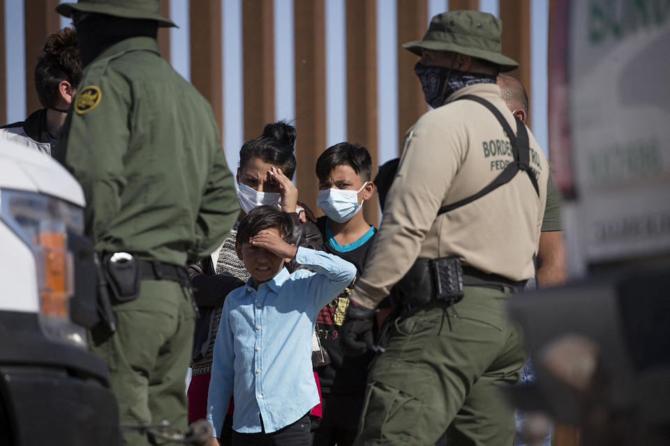 Young migrants from Colombia wait to be processed after turning themselves over to authorities at the United States and Mexico border May 12, 2021 in Yuma, Arizona. / Credit: RINGO CHIU/AFP via Getty Images
