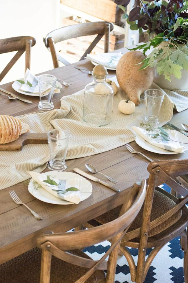 """<p>A neutral, textured table runner serves as an elegant backdrop for small white gourds, as shown in this dining table by <a href=""""http://www.unexpectedelegance.com/5-ways-to-update-your-dining-room-table/"""" target=""""_blank"""">Unexpected Elegance</a>.</p>"""