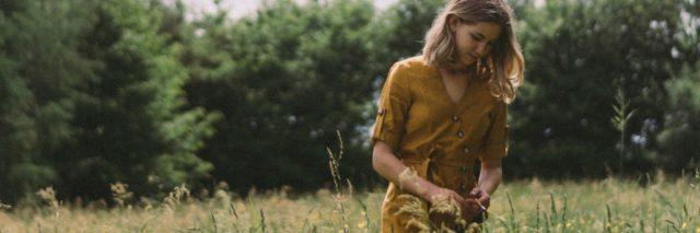photo of blonde woman in yellow dress standing in field of wildflowers