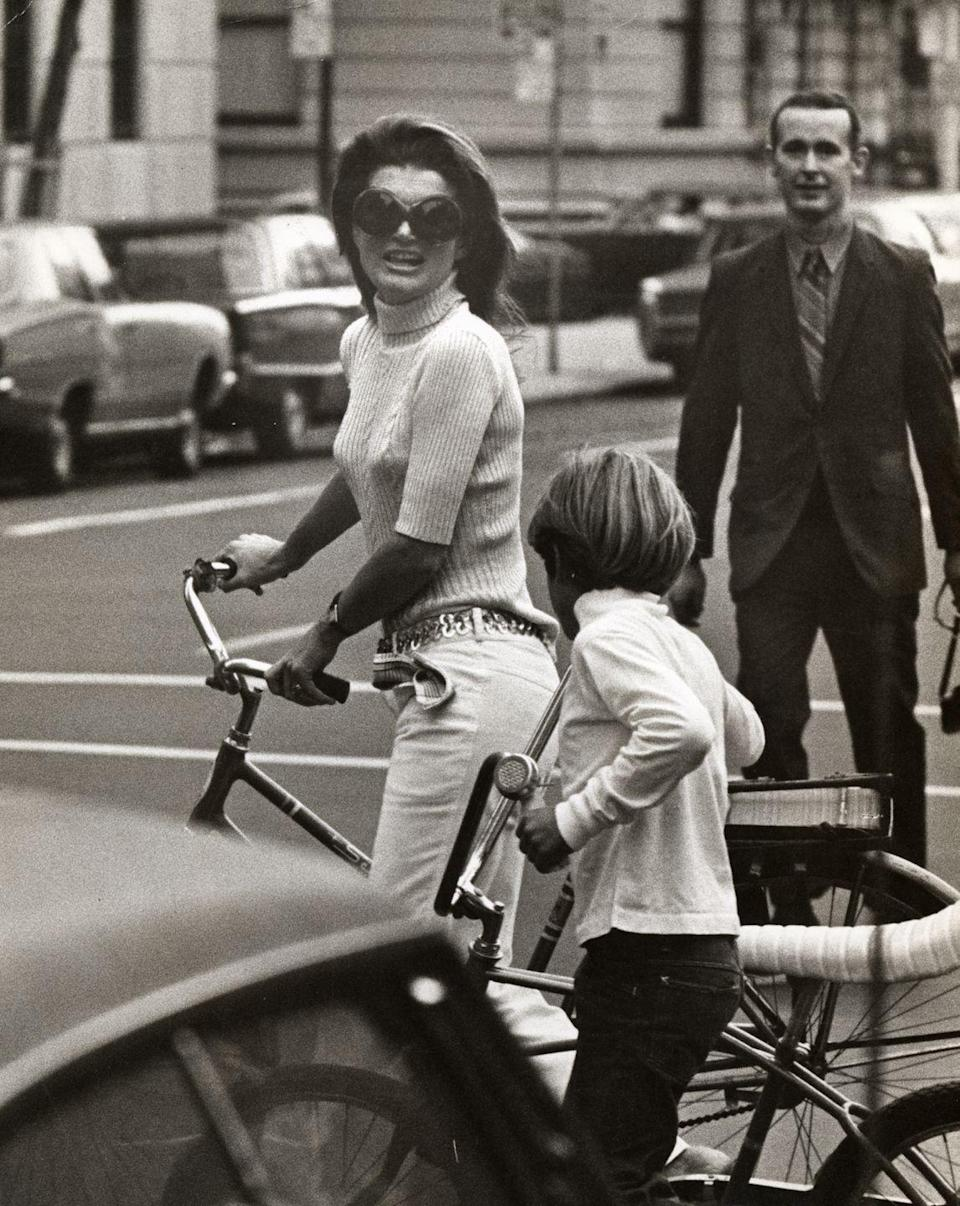<p>Wearing a knit turtleneck and belted white jeans, Jackie and John Jr. take a bike ride in New York City. <br></p>