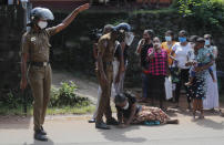 A family member of an inmate pleads lying at the feet of a policeman demanding to know the condition of her relative outside the Mahara prison complex following an overnight unrest in Mahara, outskirts of Colombo, Sri Lanka, Monday, Nov. 30, 2020. Sri Lankan officials say six inmates were killed and 35 others were injured when guards opened fire to control a riot at a prison on the outskirts of the capital. Two guards were critically injured. Pandemic-related unrest has been growing in Sri Lanka's overcrowded prisons. (AP Photo/Eranga Jayawardena)