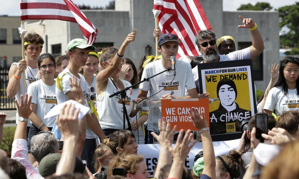 "<span class=""element-image__caption"">David Hogg, center, a survivor of the school shooting at Marjory Stoneman Douglas high school, in Parkland, Florida, addresses a rally in front of the headquarters of gun manufacturer Smith & Wesson in Springfield, Massachusetts on 26 August.</span> <span class=""element-image__credit"">Photograph: Steven Senne/AP</span>"