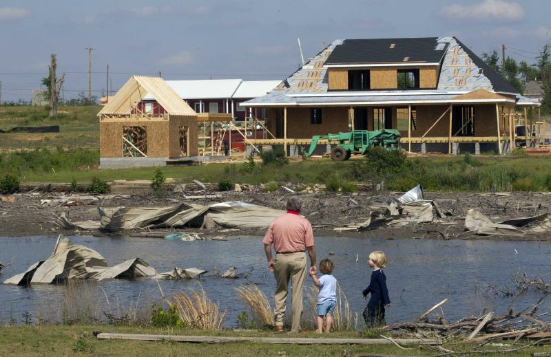Bill Trick walks with his grandchildren Caleb and Cole as they look at the destruction that remains around Forest Lake in Tuscaloosa, Ala., Friday, April 27, 2012. A year ago 62 tornadoes swept across the state, killing 253 people. (AP Photo/Dave Martin)