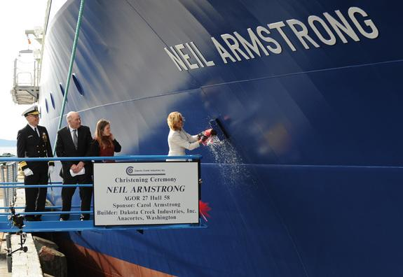Carol Armstrong, ship's sponsor for the Auxiliary General Oceanographic Research (AGOR) research vessel (R/V) Neil Armstrong (AGOR 27), breaks a bottle across the bow during a christening ceremony at Dakota Creek Industries, Inc. shipyard in An