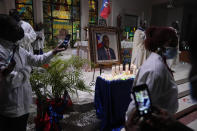 Mourners take pictures of electric candles resting in front of a portrait of Haiti's assassinated President Jovenel Moïse, during a memorial service at Notre Dame d'Haiti Catholic Church on Thursday, July 22, 2021, in the Little Haiti neighborhood of Miami. Miami's Haitian Consul General hosted the service for members of the city's large Haitian community to pray for the troubled nation and pay their respects to the president, who was slain in a July 7 attack at his home which left his wife seriously wounded. (AP Photo/Rebecca Blackwell)