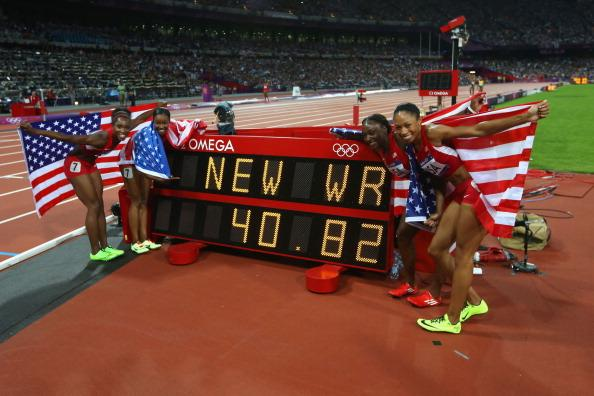 LONDON, ENGLAND - AUGUST 10:  Carmelita Jeter of the United States, Bianca Knight of the United States, Allyson Felix of the United States and Tianna Madison of the United States celebrate next to the clock after winning gold and setting a new world record of 40.82  afterthe Women's 4 x 100m Relay Final on Day 14 of the London 2012 Olympic Games at Olympic Stadium on August 10, 2012 in London, England.  (Photo by Streeter Lecka/Getty Images)