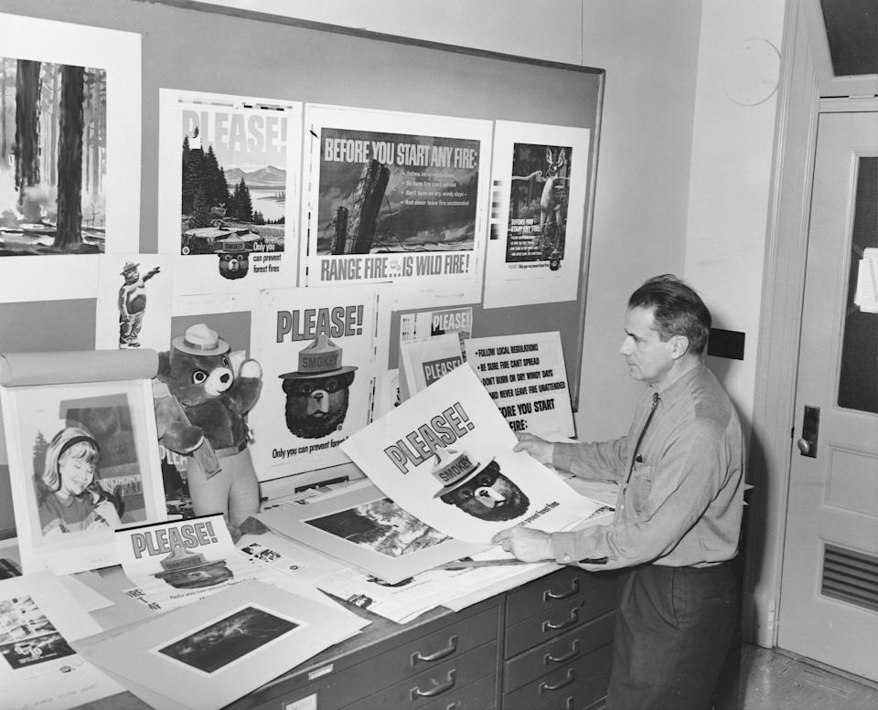 A park ranger in an office with a plethora of posters about preventing forest fires, most of which feature Smokey the Bear.  (Photo: Corbis via Getty Images)