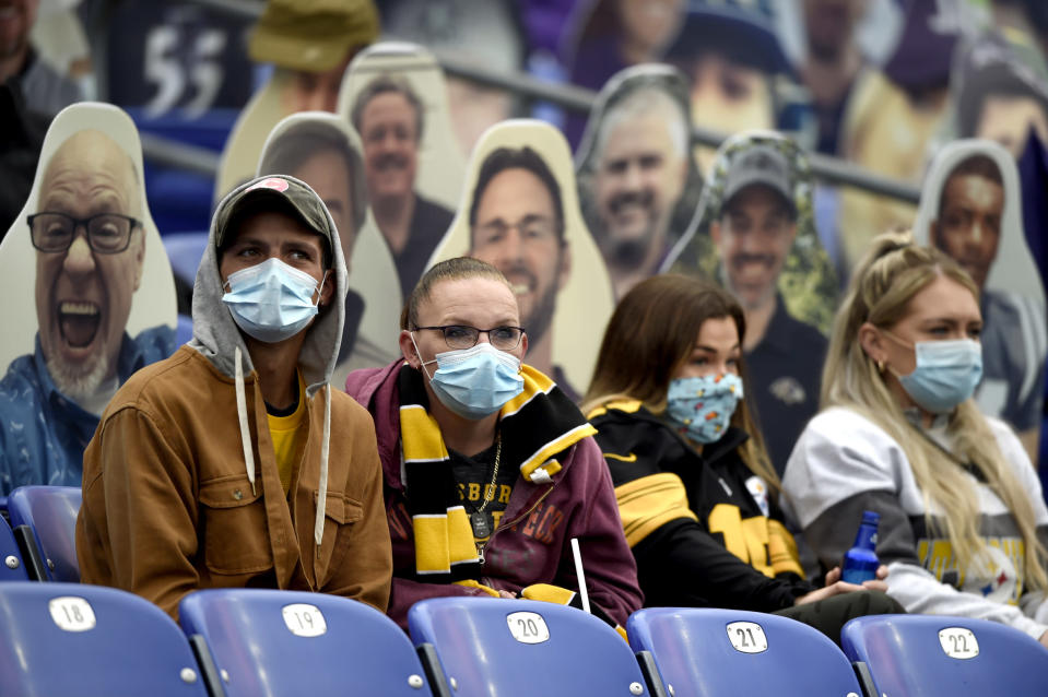 FILE - In this Nov. 1, 2020, file photo, specators wear a face masks to protect against COVID-19 during the first half of an NFL football game between the Baltimore Ravens and the Pittsburgh Steelers, in Baltimore. A new set of rules are coming in just about every sport, almost all with enhanced health and safety in mind. If they work, games could get out of bubbles and return to arenas and stadiums with some fans in attendance sometime soon. Perhaps more importantly, they could also provide some common-sense solutions to virus issues in the real world.(AP Photo/Gail Burton, File)