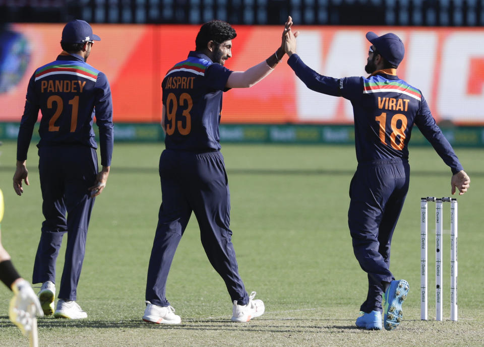 India's Jasprit Bumrah, centre, is congratulated by teammate Virat Kohli after taking the wicket of Australia's Aaron Finch during the one day international cricket match between India and Australia at the Sydney Cricket Ground in Sydney, Australia, Friday, Nov. 27, 2020. (AP Photo/Rick Rycroft)
