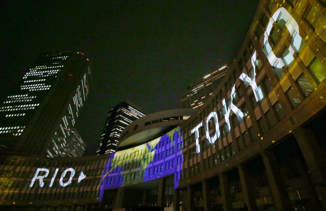 FILE - In this July 24, 2017, file photo, images are illuminated on the Tokyo Metropolitan Government building during the Tokyo 2020 flag tour festival for the 2020 Games in Tokyo. Tokyo has billed itself as a safe pair of hands and is everything that Rio de Janeiro wasnt during the last Summer Olympics. Rio left behind scandals, millions in unpaid bills, and empty white elephant venues. (AP Photo/Shizuo Kambayashi, File)