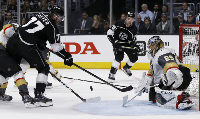 A shot by Los Angeles Kings center Jeff Carter, second from left, gets in front of Vegas Golden Knights goaltender Marc-Andre Fleury, right, on a centering pass from center Tobias Rieder (10), of Germany, during the second period of Game 4 of an NHL hockey first-round playoff series in Los Angeles, Tuesday, April 17, 2018. (AP Photo/Alex Gallardo)