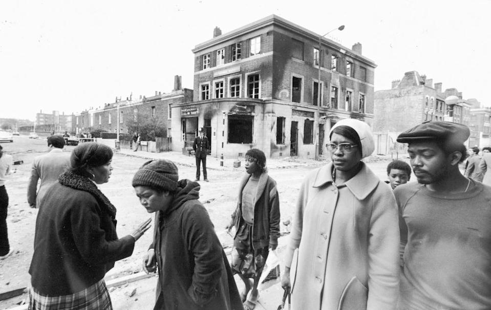 Local residents walk past a burned-out pub in Brixton after a second night of rioting in the area, 13 April 1981.