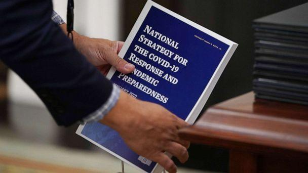 PHOTO: An aide collects copies of the National Strategy for COVID-19 before President Joe Biden speaks in the State Dining Room of the White House in Washington, Jan. 21, 2021. (Mandel Ngan/AFP via Getty Images)