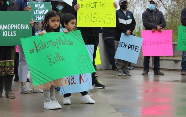 A young child holds a sign with the message 'Islamophobia kills' during a vigil in Yellowknife' for the victims of the attack in London.