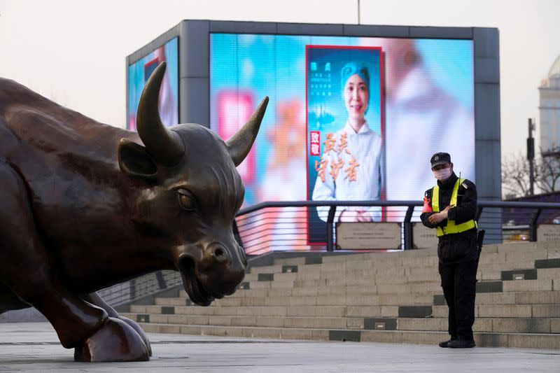 FILE PHOTO: Security guard wearing a face mask stands near the Bund Financial Bull statue and a display showing an image of a medical worker on The Bund in Shanghai